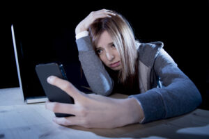 worried teenager using mobile phone and computer as internet cyb