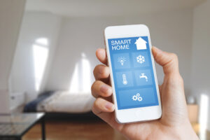 Smart home automation app on smartphone hold by female's hand